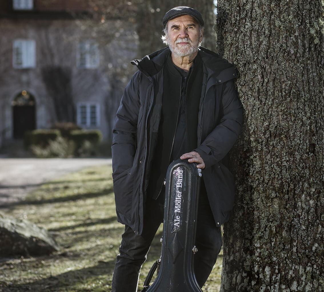 Ale Möller står vid träd med gitarr